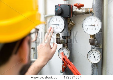 maintenance - technician checking pressure meters for house heating system
