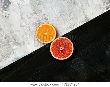 Grapefruit, mandarin - citrus fruits halves on wooden background.