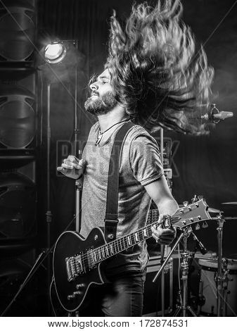 Photo of a young man playing electric guitar on stage and tossing his long hair around.
