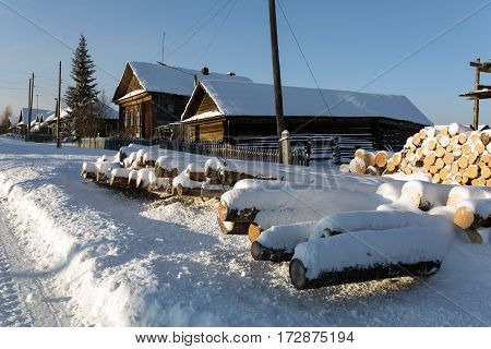 Snow-covered old wooden houses and heaps of firewood in a russian old believer village Visim. Ural region, Russia.