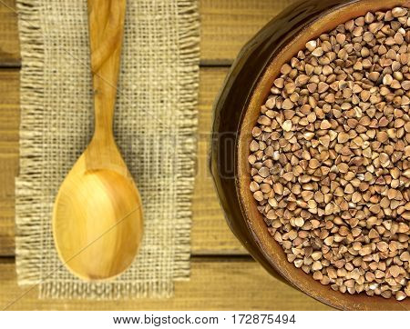 Buckwheat groats in a bowl and wooden spoon