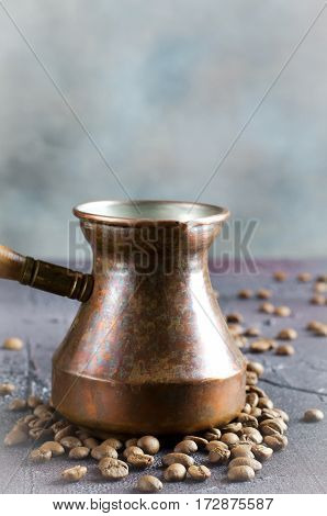 Old copper coffee pot and coffee beans on dark rustic background, vertical