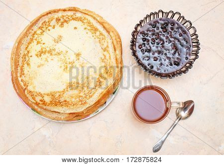 Pancakes with raspberry jam and tea on the table. Maslenitsa Festival