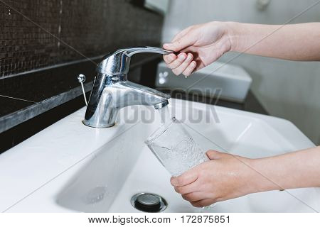 Woman Filling A Glass Of Water From A Stainless Steel Or Chrome Tap