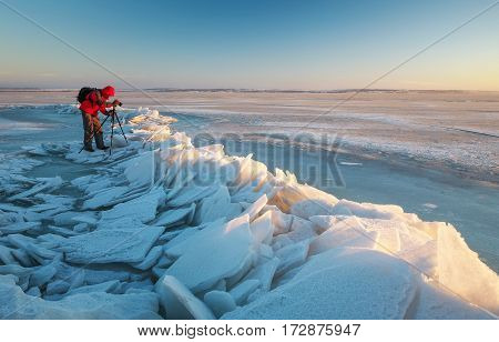 Photographer take a pictures on the coast of frozen river in winter