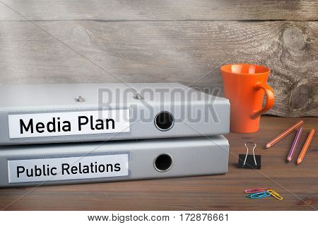 Public Relations and Media Plan - two folders on wooden office desk.