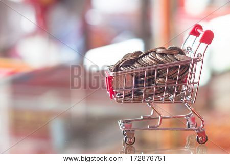 Finance and money concept mini shopping cart red blurry background
