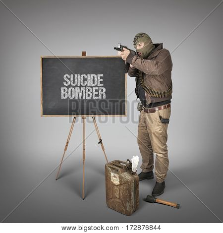 Suicide bomber text on blackboard with terrorist holding machine gun