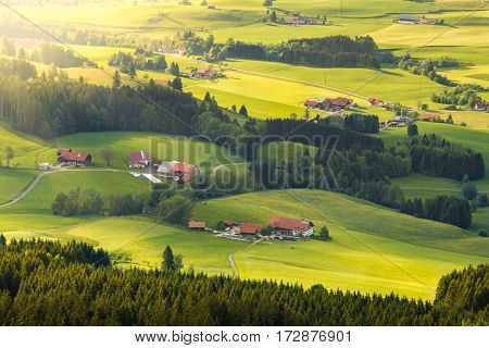 Lovely rural countryside in beautiful sunlight. Pasture landscape with barnyards. Peaceful atmosphere of a typical bavarian cultured landscape.