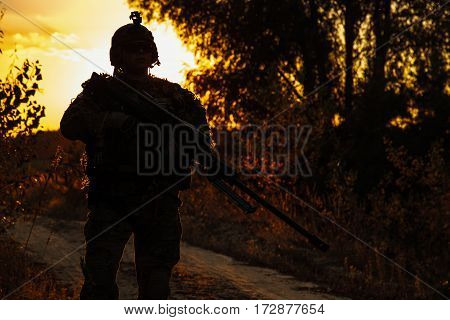 Army sniper with large-caliber rifle in the forest. Front view portrait, silhouette foliage background. Servicemen on guard of national security