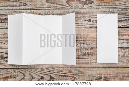 Four - fold white template paper on wood texture