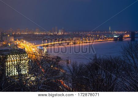 Podol region of Kiev and frosted Dnieper river evening view with illumination. Little Saint Nicolas church on the water also is seen on image.