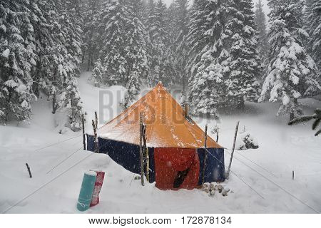 Big bright tourist tent against winter forest background. Big bright tourist tent against winter forest background.
