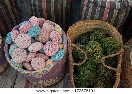 Multicolored pumice in striped sack and green dry algae in wicker basket. Arab souvenirs.