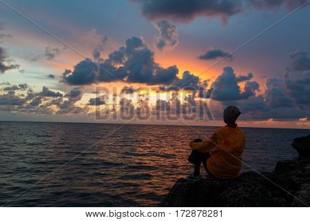 Woman dressed in orange anorak is sitting on rock and contemplating beautiful sunset over sea.
