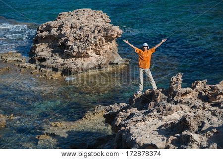 Woman dressed in orange T shirt with outstretched hands situated in rock. Clear sea in background.