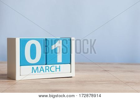 March 1st. Day 1 of month, wooden color calendar on white background. Spring time, empty space for text.