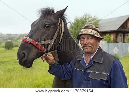 An elderly farmer with his horse in the rain. Old-believer village Visim, Russia.