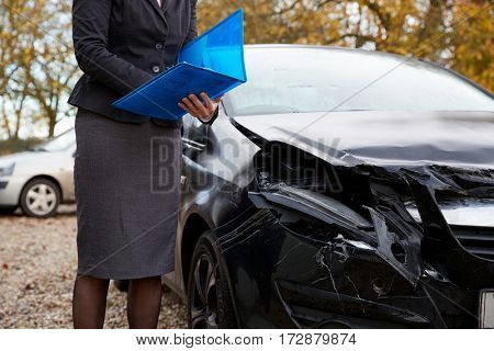 Female Loss Adjuster Writing Report On Damaged Car