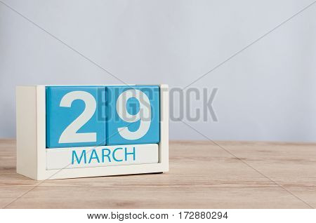 March 29th. Cube calendar for march 29 on wooden surface with empty space For text.