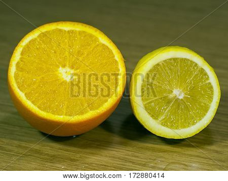The orange and lemon on a wooden surface