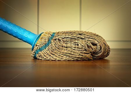 old dirty plastic mop on wooden floor cleaning the parquet