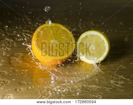 The orange and lemon on a wooden surface with waterdrops