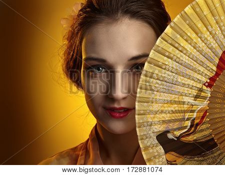 Young Beautiful Woman In Traditional Japanese Kimono With Fan