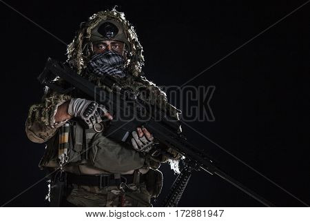 Army sniper with big rifle standing on black background. Face is painted with warpaint. Backlit contour silhouette shot