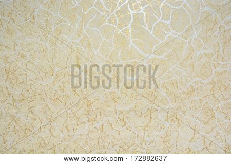 Closeup surface of wall with beige and golden cracks pattern as background