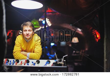 young men in evening bar play kicker. in the yellow jacket. He concentrated on the game