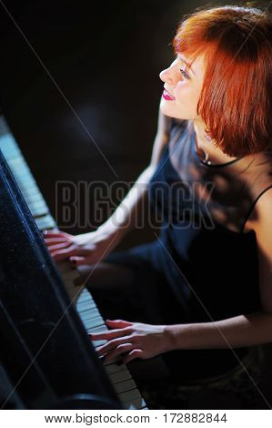 The girl a pianist plays the piano. The beautiful smiling face of a beam of bright light closeup.