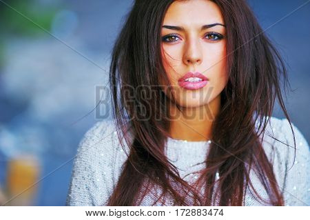 Portrait of a pretty brunette girl with beautiful expressive eyes and long hair flying with the wind closeup