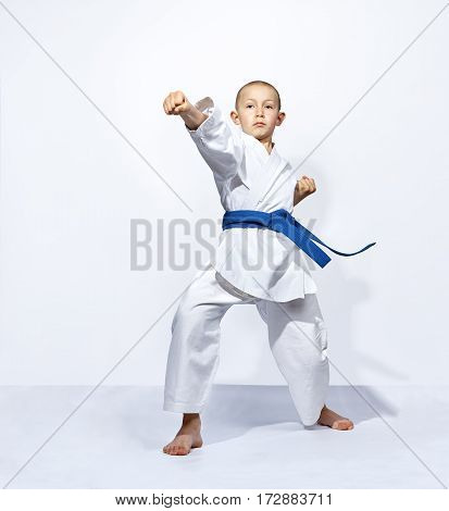 Straight punch arm karateka is beating with a blue belt