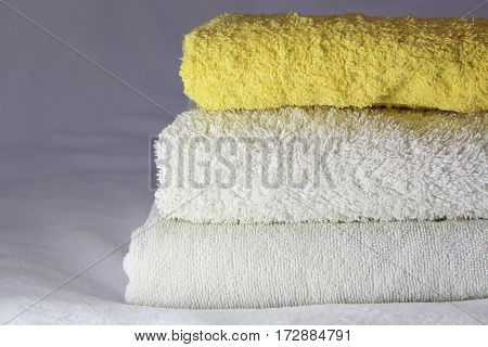 close up fresh, yeliow and white towels,placed on the bed inside of the hotel room
