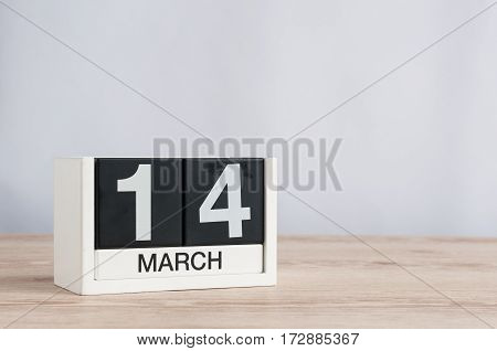 March 14th. Image of march 14 wooden color calendar with flower on white background. Spring day. Commonwealth and International pi Day.