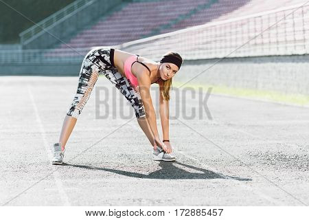 Sport, exercises outdoors. Girl in rose top and black and white leggins doing stretching on stadium. Bending to toes. Full body, looking aside
