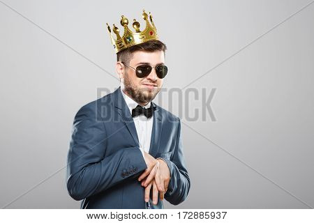 Stylish young man in suit with bow and sunglasses. Wearing crown. Hands together, funny posture. Outrageous, fancy look. Waist up, studio, indoors
