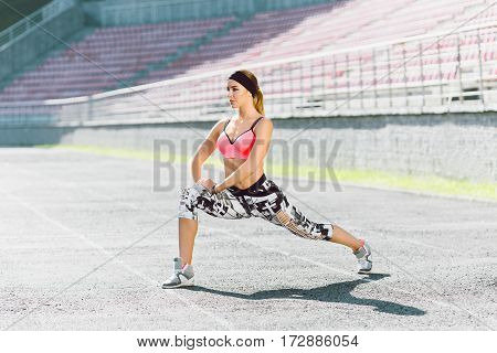 Sport, exercises outdoors. Girl in rose top and black and white leggins doing stretching on stadium. One leg ahead, one aside. Full body, profile