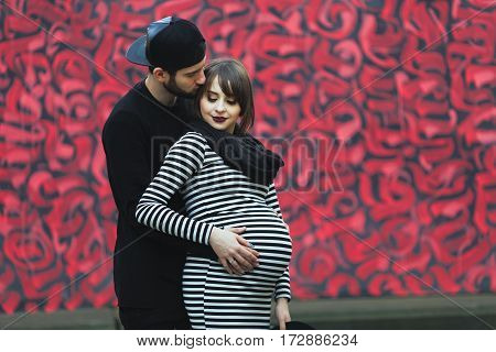 Man holding hand on stomach of pregnant woman. Standing behind her and kissing. Colorful background. Young couple, love story, pregnant girl. Outdoors, full body, point of view