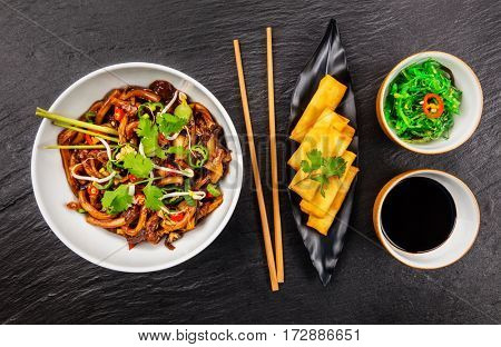 Asian noodles with spicy soy sauce, chicken pieces and spring rolls, top view, served on black stone.