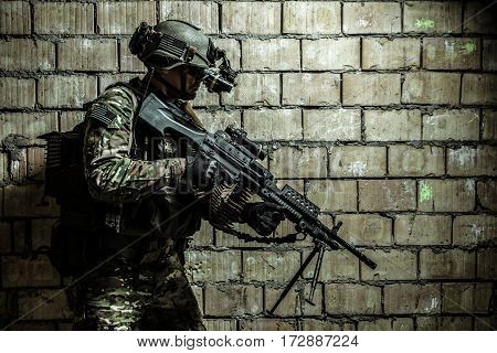 US Army Ranger member with machinegun and night vision goggles moving along the wall during mission