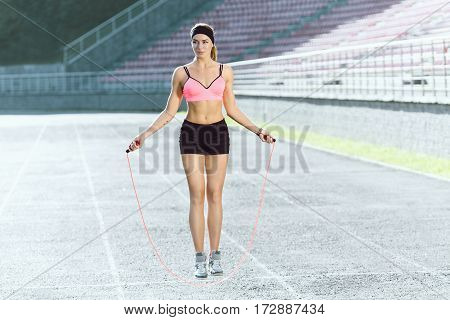 Sport, exercises outdoors. Girl in rose top and black shorts jumping on skipping rope on stadium. Sporty girl in good shape, full body, looking aside