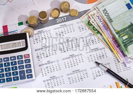 2017 Calendar, Pen, Euros Bills And Calculator Placed On A Table.