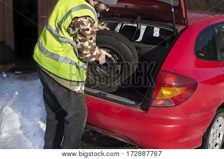 The man pulls out a spare wheel from the trunk of a car wearing a reflective vest. Replacing the spare wheel in winter conditions.