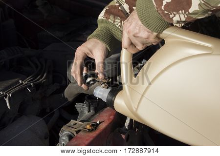 Mechanic pouring coolant to the radiator.  Male lists the coolant in the cooling system.