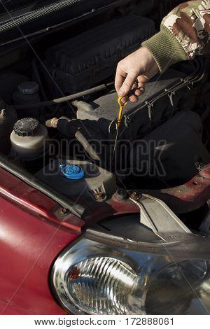 The mechanic checks the engine oil level dipstick