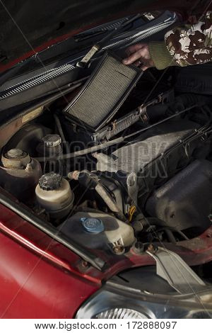 The mechanic pulls out the old air filter.  Replacing the air filter in your car.