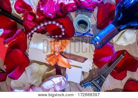 holiday concept - roses petals money bottles of wine a box of jewels and Eiffel Tower.