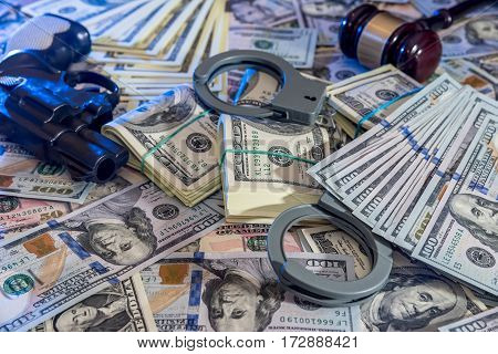 handcuffs and judge gavel gun and money on brown wooden table.